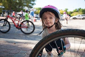 Sarah Begley, 4, of Columbia, checks the bike tires before riding with her dad Shawn and brother Noah. Photos at the 2012 Columbia Bike About, September 15.