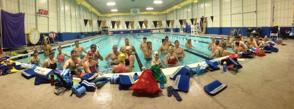 group of swimmers standing and posing an indoor pool