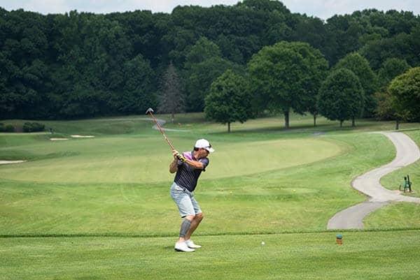 man swinging club on golf course