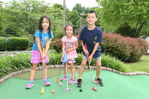 2 girls and a boy posing on put put golf course