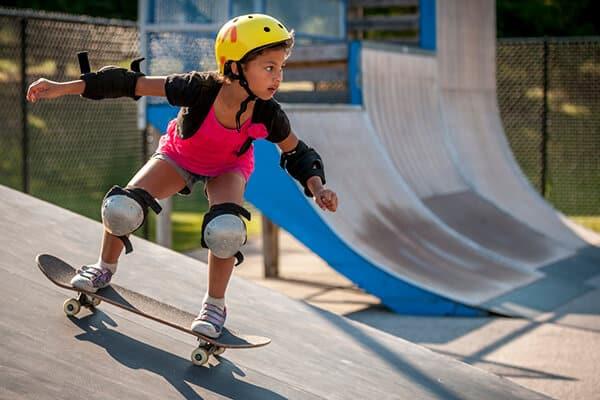 Little girl on skateboard at summer camp
