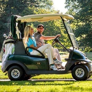 man and woman riding in golf course