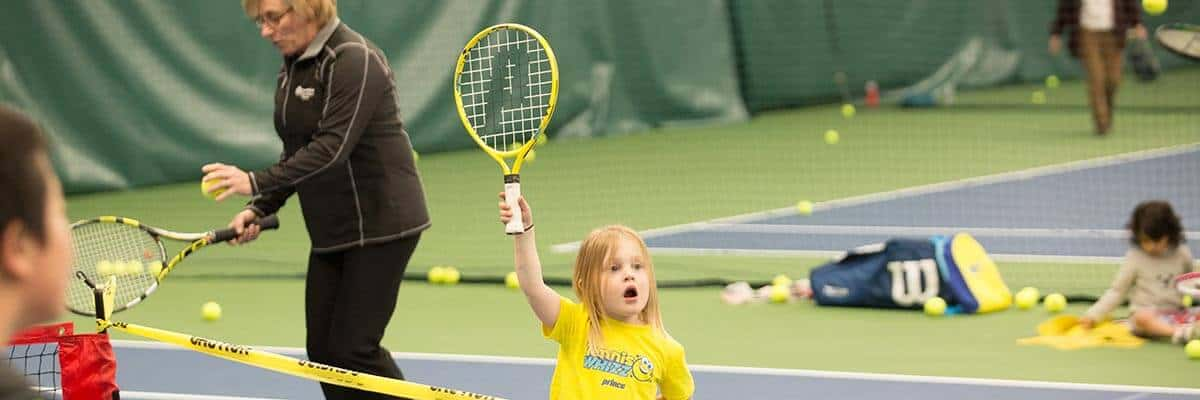 little girl with racket raised over her head