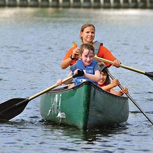 a little boy girl and lady canoeing