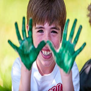 a boy holding up both of his hands with green paint on them