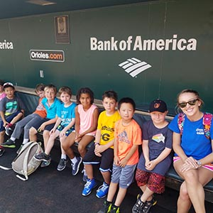 group of kids sitting and posing at an Orioles game