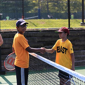 two kids shaking hands at the net