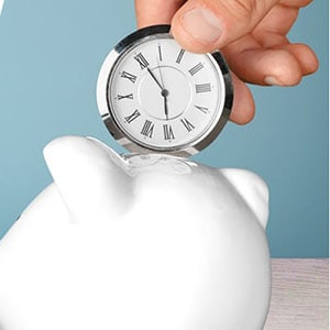 a hand placing a small clock into a piggy bank