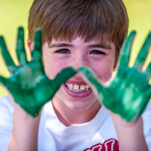 young man at art camp with green paint on both hands