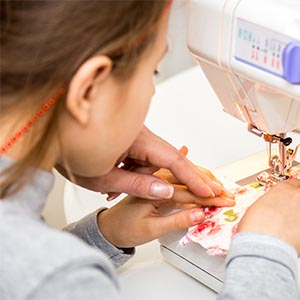 young girl sewing on a machine with camp director assistance