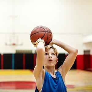 young boy shooting a basketball