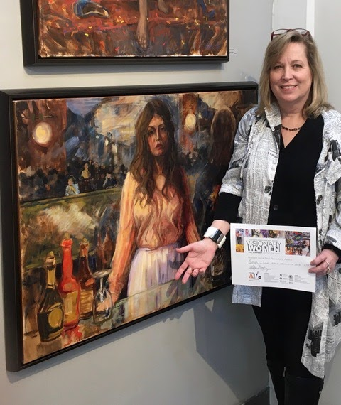 amela Wilde with painting in Columbia Art Center Gallery