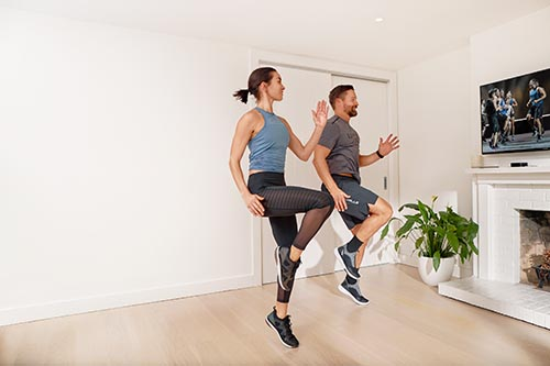 man and lady exercising to les mills video at home