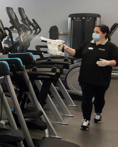 lady spraying sanitizer on fitness equipment